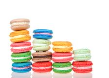 Stacks of macaron cookies isolated on reflective surface. Macaron cookies in tiny white dishes stacked in graduated rows, colorful traditional french pastry stock photos