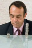 Stacks of Money. Businessman staring dejectedly at a shorter stack of coins to his right while a larger stack stands off to the right Royalty Free Stock Photography