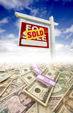 Stacks of Money Fading Off and Sold Sign. Stacks of Money Fading Off and Sold For Sale Real Estate Sign Against Blue Sky with Clouds royalty free stock image