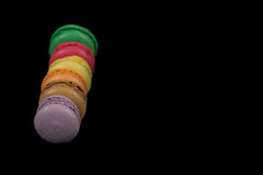 Stacks of multicolored macaroon isolated on black background. Frame royalty free stock photo