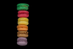 Stacks of multicolored macaroon isolated on black background. Frame stock photography