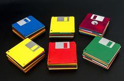 Stacks of Old Floppy Disks. Horizontal shot of six stacks of multicolored plastic disks on a black background.  Some of the stacks are angled out.  The middle Royalty Free Stock Images