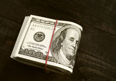 Stacks of one hundred dollars banknotes. On wooden background close-up Royalty Free Stock Image