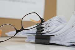 Stacks of paper files with clips and glasses stock photo
