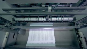 Paper piling on a conveyor, top view. Stacks of paper on a line stock footage