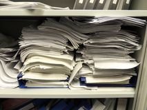 Stacks of paperwork in overflowing cupboard. Office papers in disorganised piles on a shelf in an office. Heaps of paper like this should be a thing of the past Stock Images