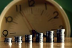 Stacks or pile of coins and a clock Royalty Free Stock Photography
