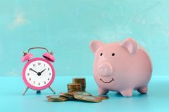 Stacks and a pile of coins, a pink alarm clock and a piggy bank on a turquoise background. The symbol of the. Accumulation of money. Beautiful bright photo Royalty Free Stock Photos