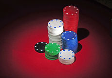 Stacks of poker chips on playing table. Several stacks of casino poker chips of various heights and colors sitting on a red colored playing table. The light in Royalty Free Stock Photos