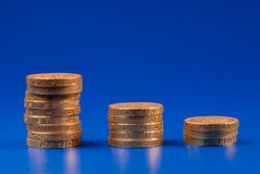 Stacks of pound coins. Descending stacks of coins on blue background Royalty Free Stock Photography