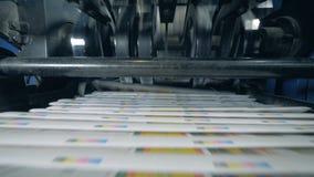Stacks of printed newspaper on a conveyor, print office equipment. 4K stock footage
