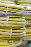 stacks of rolls yellow pvc plastic pipe on the counter in the store. Sale Hoses in the garden of various manufacturers, on shelves stock image