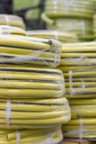 Stacks of rolls yellow pvc plastic pipe on the counter in the store. Sale Hoses in the garden of various manufacturers, on shelves. In store. Hose for watering royalty free stock images