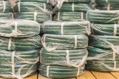 Stacks of rolls yellow pvc plastic pipe on the counter in the store. Sale Hoses in the garden of various manufacturers, on shelves. In store. Hose for watering stock photos