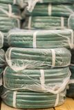 Stacks of rolls yellow pvc plastic pipe on the counter in the store. Sale Hoses in the garden of various manufacturers, on shelves. In store. Hose for watering royalty free stock photo