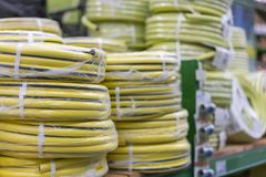 Stacks of rolls yellow pvc plastic pipe on the counter in the store. Sale Hoses in the garden of various manufacturers, on shelves. In store. Hose for watering royalty free stock photography