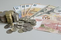 Stacks of Ruble coins on Euro Dollar Ruble banknotes on solid color background.  Royalty Free Stock Photography