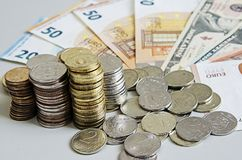 Stacks of Ruble coins on Euro Dollar Ruble banknotes on solid color background.  Stock Image