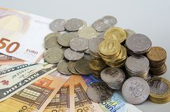Stacks of Ruble coins on Euro Dollar Ruble banknotes on solid color background.  Royalty Free Stock Photos