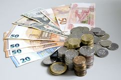 Stacks of Ruble coins on Euro Dollar Ruble banknotes on solid color background.  Stock Images