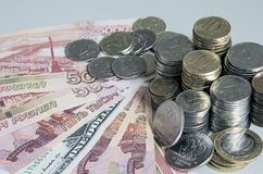 Stacks of Ruble coins on Euro Dollar Ruble banknotes on solid color background.  Stock Photos