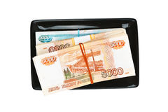 Stacks of russian banknotes on black plate Stock Photo