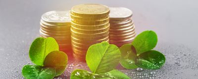 Stacks of Russian coins with clover leaves on a gray background with droplets of water. St.Patrick's Day. Stacks of Russian coins with clover leaves on a gray stock photo