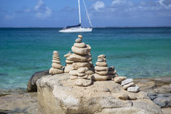 Stacks of stones in balance at a beach with yacht on background Stock Photos