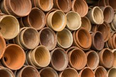 Stacks of terracotta flowerpots in a gardeners potting shed at botanical garden. Many stacked ceramic pots for plants. Old ceramic. Pots stock photos