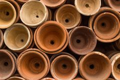 Stacks of terracotta flowerpots in a gardeners potting shed at botanical garden. Many stacked ceramic pots for plants. Old ceramic. Pots royalty free stock photo
