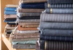 Stacks of textiles in close up view. Close up view of fabrics stacks on shelf in tailor workshop Royalty Free Stock Image