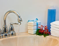 Stacks of Towels and Soap. By a lavatory with water running Stock Images