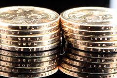 Stacks of US One Dollar Coins. Two stacks of US one dollar gold coins on a mirror royalty free stock photos