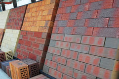 Stacks of various colored concrete pavers (paving stone) or patio blocks organized on pallets and for sale Stock Image
