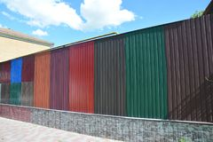 Stacks of various colorful metal fence panels and metal roof sheets for sale. stock photos