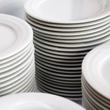 Stacks of white plates. Piles of stacked white plates Stock Photo