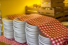 Stacks of white plates under a checkered red and white tableclot. H in the restaurant Stock Photography