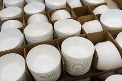 Stacks of white and round shaped porcelain bowls in corrugated b Royalty Free Stock Images