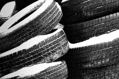 Stacks of Worn Tires in the Snow Stock Photo