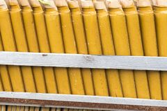 Stacks of yellow ceramic glazed curved roof tiles in a symmetrical pattern. Typical in Asia for roof construction stock photo