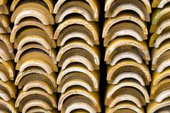 Stacks of yellow ceramic glazed curved roof tiles in a symmetrical pattern. Typical for construction of roofs in Asia royalty free stock photos