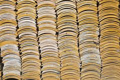 Stacks of yellow ceramic glazed curved roof tiles in a symmetrical pattern. Typically used in Asia for roofs stock photography