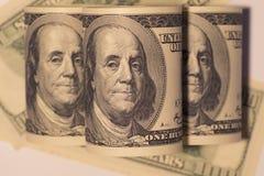 Staczający się w górę sto dolarowych rachunków Zdjęcia Stock