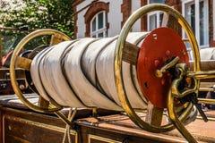 Staczający się w górę węża elastycznego dziejowy pożarniczy silnik jednostka straży pożarnej przy oldtimer wystawą obraz royalty free