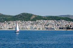 Stad av Kavala Grekland som beskådas från färjan liten segelbåt Arkivfoto