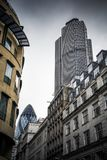 Stad av London byggnader med två skyskrapor under lynnig himmel Fotografering för Bildbyråer
