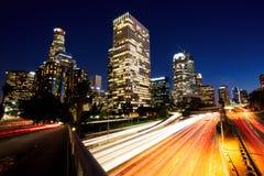 Stad av Los Angeles som är i stadens centrum på solnedgången med ljusa slingor Royaltyfria Foton