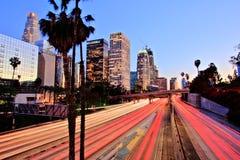 Stad av Los Angeles som är i stadens centrum på solnedgången med ljusa slingor Royaltyfri Foto