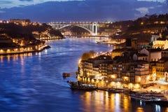 Stad av Porto vid den Douro floden på natten i Portugal Arkivfoton