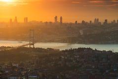 Stad bij zonsondergang met oranje hemel en brug Stock Afbeeldingen